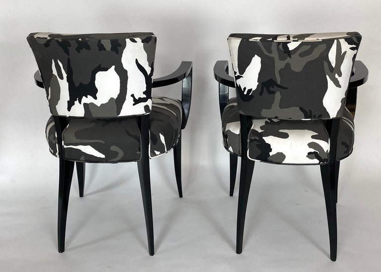 Pair of French 1940s bridge armchairs. Restored with a black lacquered finish and recovered with urban camouflage fabric. A classic armchair with a twist.