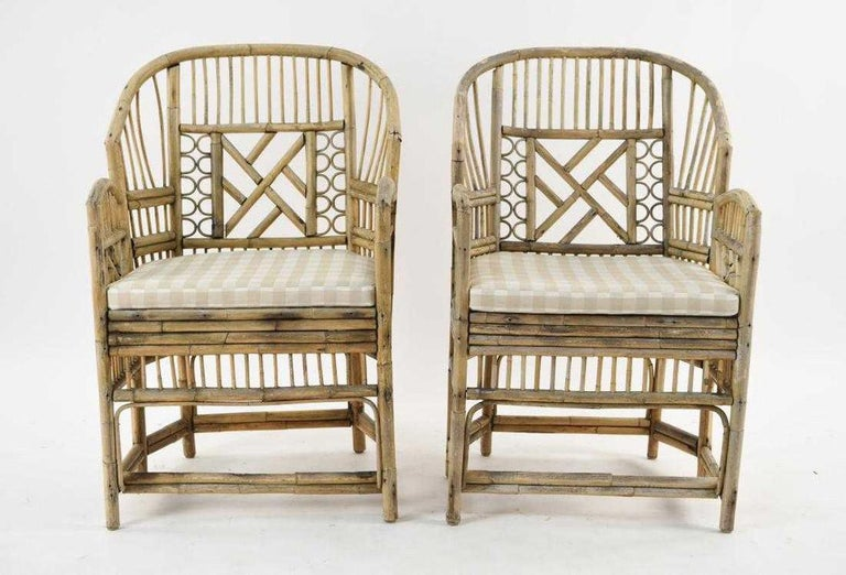 The stylish pair of bleached bamboo chairs have plaid cushions over woven raffia seats. These add style to either indoor or outdoor settings.  Bamboo shows weathering from previous outdoor use.  Keywords: Tortoise or bamboo chairs, rattan, wicker,