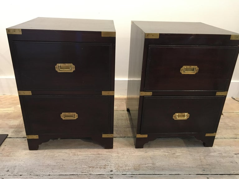 A pair of handsome rosewood finished British Campaign style bedside or sofa side tables. Brass strap corners and flush brass drawer pulls typical of the campaign style. Two pull-out drawers for storage. Late 1900s. There are few superficial