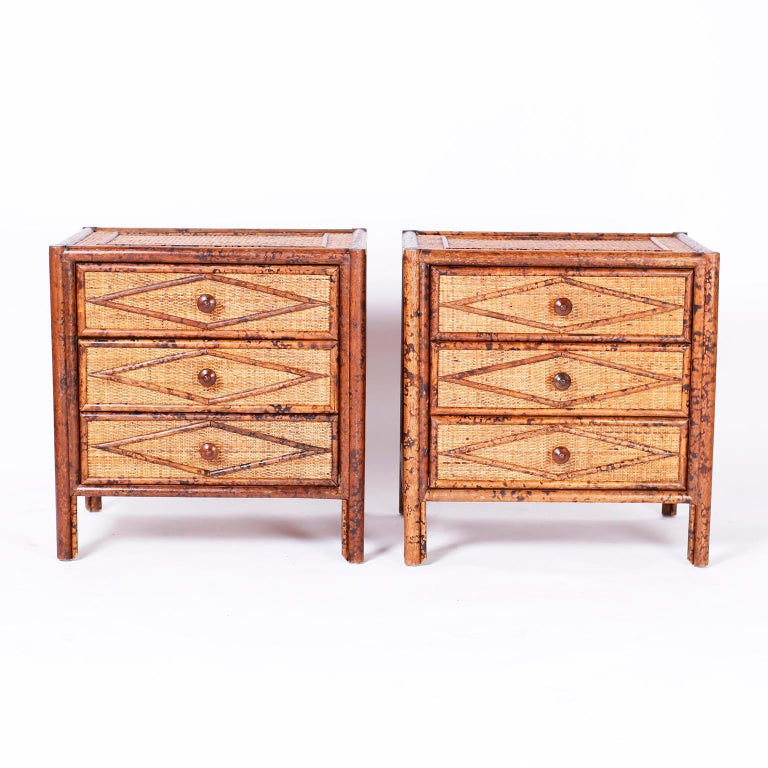 Pair of British Colonial three-drawer stands or chests with faux burnt bamboo frames, grass cloth panels on the tops, sides and front with applied bamboo geometric designs.