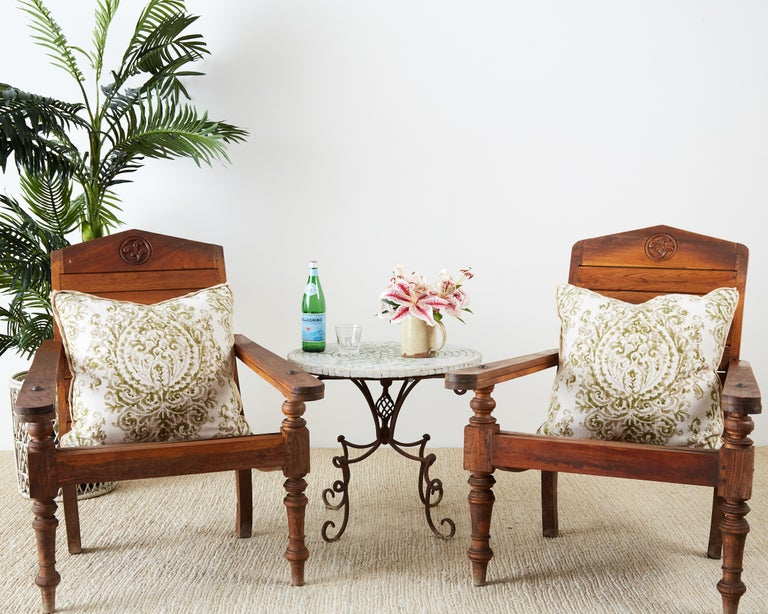 Handsome pair of hand carved teak plantation chairs made in the British Colonial style. Featuring fold-out leg supports and wood peg construction. Beautifully sculpted with a dramatic profile and ergonomic lounge seat. Supported by decorative turned