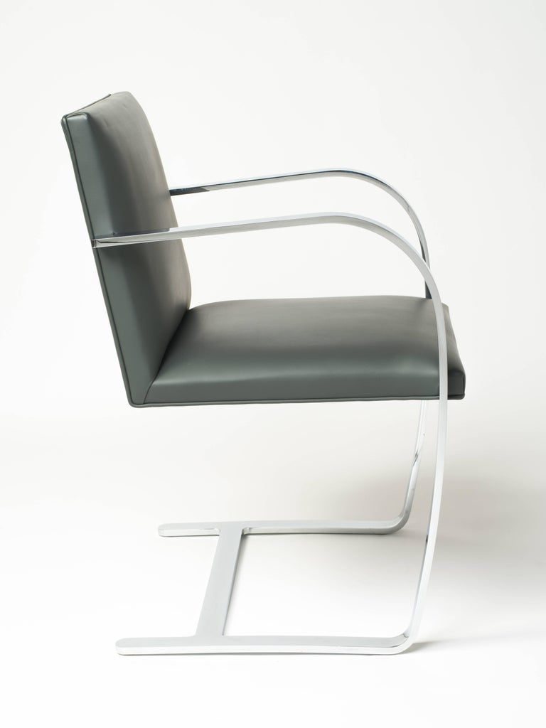 Pair of flat bar Brno chairs in elephant grey leather by Ludwig Mies van der Rohe for Knolls. Iconic Mid-Century Modern design features cantilevered steel frames with polished chrome finish. Frames have skyscraper inspired design with hidden joints