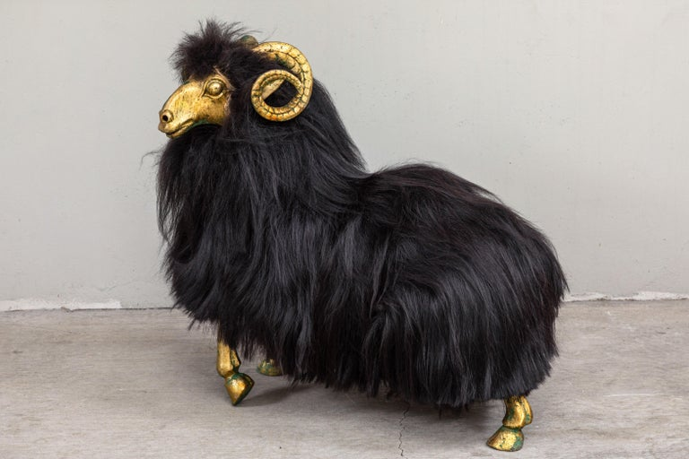 Striking pair of bronze sheep sculptures with long black Icelandic sheep fur. Whimsical and playful, these make striking statement pieces in a variety of settings.