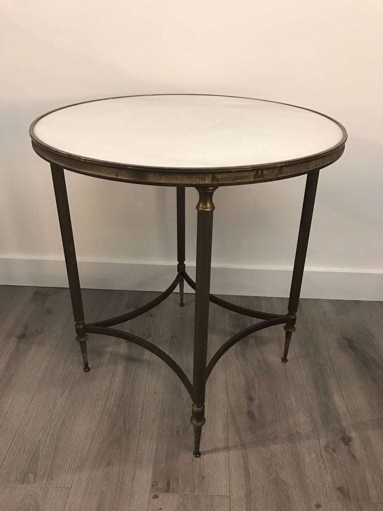 Pair of striking patinated bronze neoclassical round end tables with white marble tops.