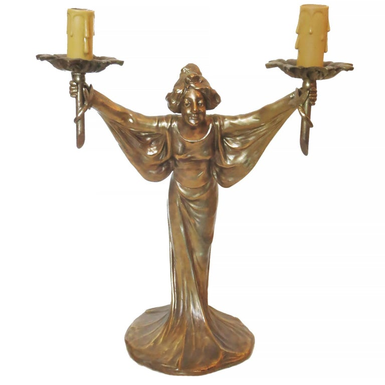 Bronze Art Nouveau style figural female candlestick candelabra lamp pair featuring a solid bronze casted figural female statue holding two candle sticks style lamps.   Product handcrafted in the USA with the highest quality materials and over 30