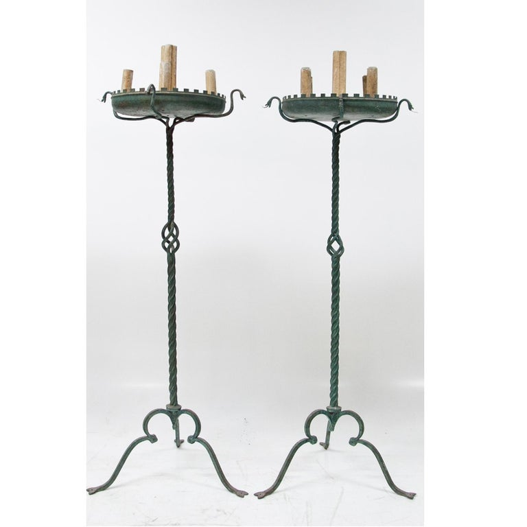 Two large bronze lamps with a twisted shaft and broad dish, resting on stylized snakes. With five sockets in total. The tongues of the snakes are partly missing.