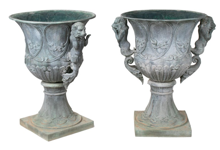 Pair of bronze garden urns with lions in old green patina.