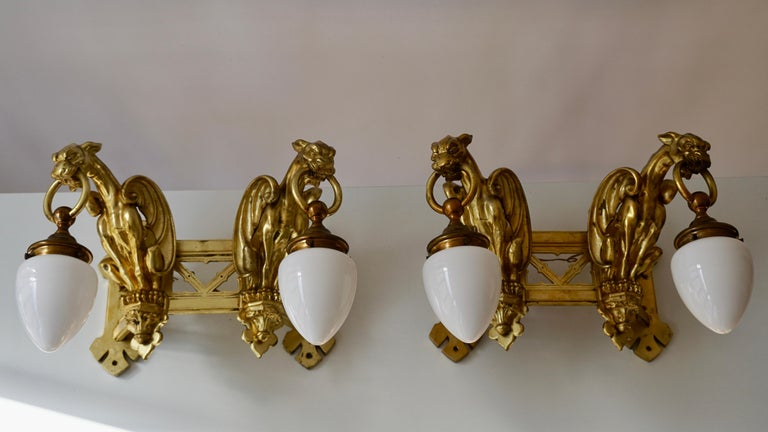 Hollywood Regency Pair of Bronze Gilt and Glass Wall Sconces Representing Two Griffins For Sale