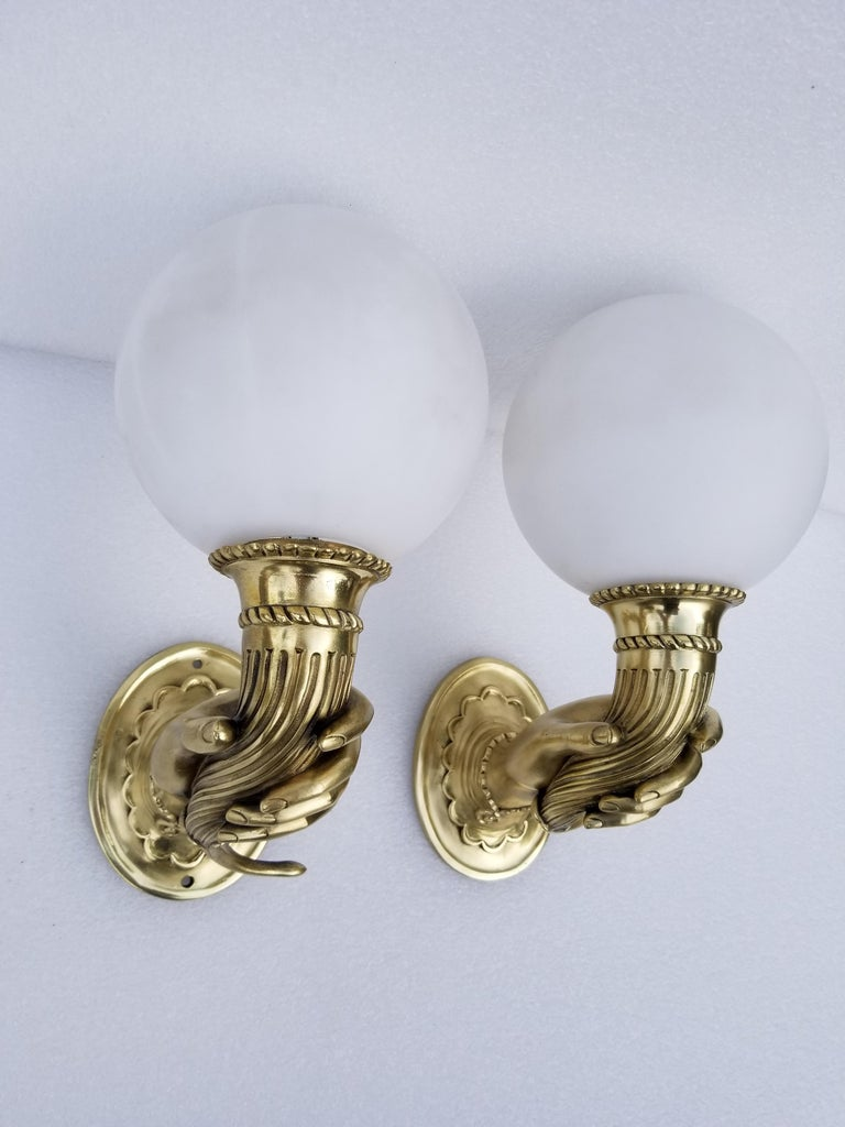 Superbe pair of bronze sconces figuring A feminine hand holding a cornucopia, rare model from 1940. Refinished and US rewired, 60 watts max bulb. New opaline globe. Back plate dimensions: 5 H, 4 W.