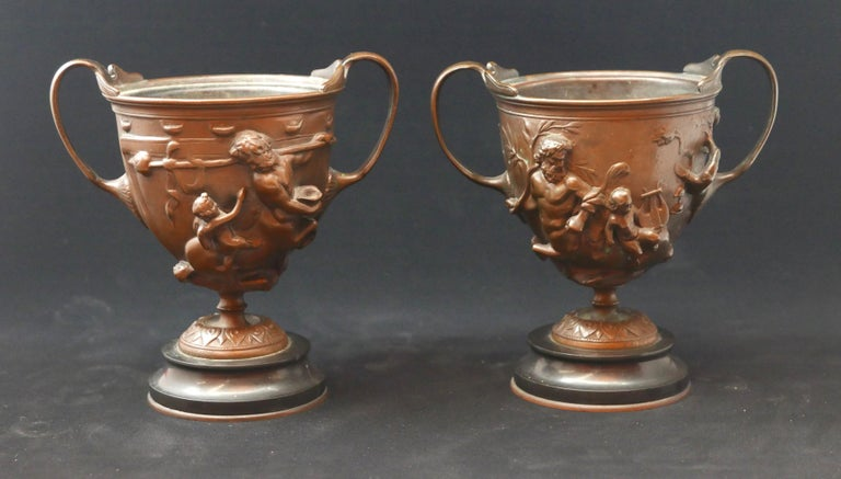 Beautiful pair of cast bronze urns by Barbedienne and attributed to the French artist Ferdinand Levillain who worked in association with the famous French foundry. Remanents of Barbedienne tag still on base.