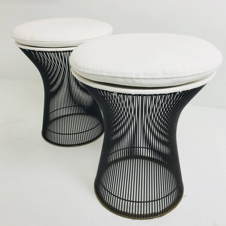 Pair of newly upholstered bronze Warren Platner stools. This iconic design features bronze wire rods with a clear coat finish and clear plastic resin on the bottoms of the bases to protect floors. The bronze is in excellent
