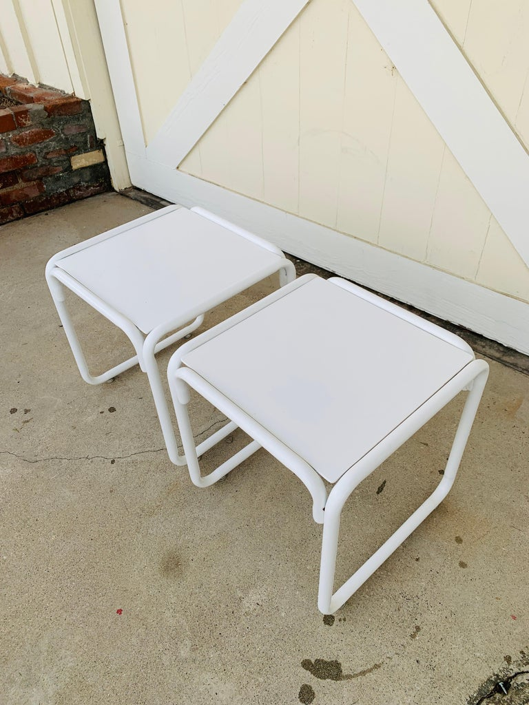 Beautiful pair of side tables designed and manufactured by Brown Jordan in the 1970s.  The table have tubular legs with a metal top powder-coated in white.  The tables are in vintage condition with some nicks and scuffs to