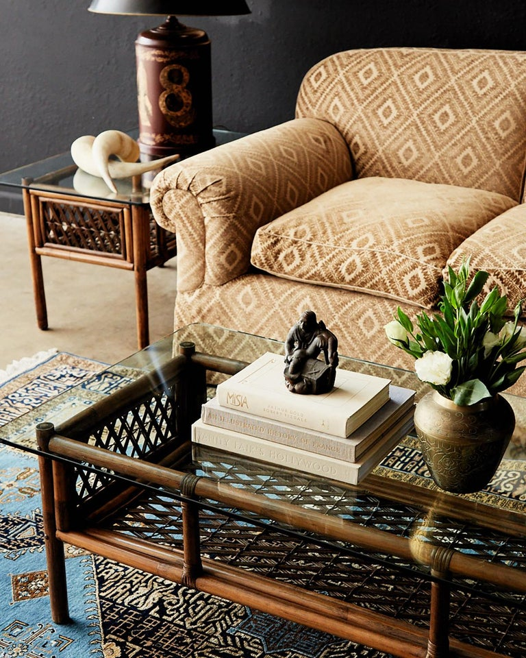 Near matched pair of bamboo rattan side or end tables made in the manner style of Brown Jordan. Almost identical but one table being 1.5 inches shorter than the other. Features a rattan frame with decorative stick wicker windows and reinforced with