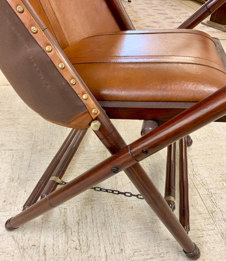 Rare Palecek brown leather Campaign folding chairs with matching ottomans/stools. Stool measures 22 inches wide x 21 inches deep x 16 inches high.