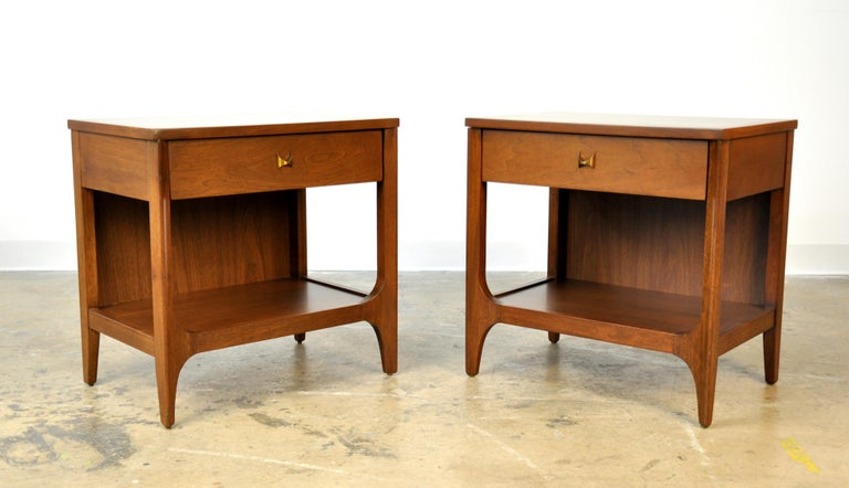 Very hard to find pair of vintage Mid-Century Modern side, end or bedside tables from the Brasilia II line manufactured by Broyhill in the 1960s. Each two-tiered occasional table is fitted with a drawer and a shelf. The drawer fronts of the