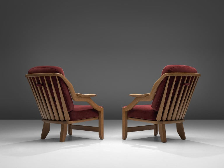 Guillerme & Chambron, pair of lounge chairs burgundy fabric and oak, France, 1950s.  This French designer duo is known for their extreme high quality solid oak furniture, from which this orange set is another great example. These chairs have a
