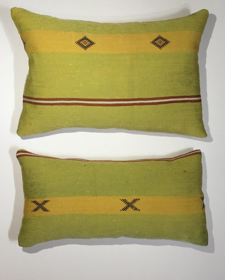 Beautiful pair of pillows made of handwoven flat-weave Kilim textile fragment, with geometric motifs, unusual funky colors of black muster and vibrant. Lime, fine cotton backing, frash new inserts.