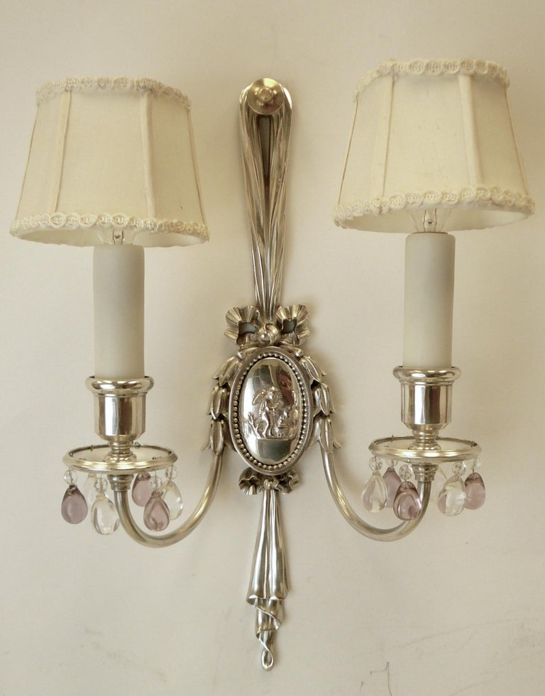 This handsome pair of sconces feature oval repousse Classical style reserves, and drapery, bow, and bellflower motifs. The twin arms are hung with clear and pale amethyst crystal drops.