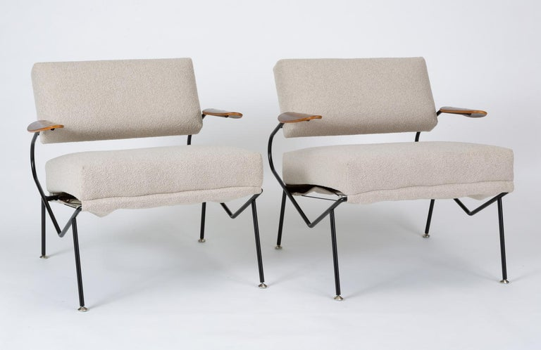 A pair of lounge chairs designed by California-based designer Dan Johnson and produced in the mid-1950s by Selig. The lightweight wire frame has a square seat- and back cushion and angled legs. Each arm has a petal-shaped armrest of molded walnut.