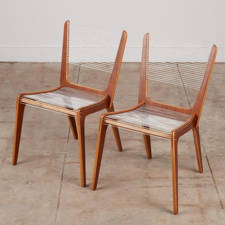 A pair of delicate accent chair by French Canadian designer Jacques Guillon. Designed in 1953, nearly transparent design consists of three interlocking wooden pieces stacked maple plywood faced with a contrasting walnut veneer joined by a wooden