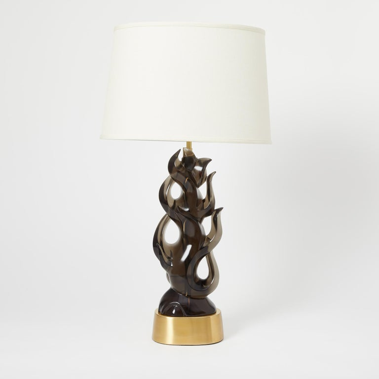 A pair of cast smokey gray tinted transparent resin table lamps in the form of a flame. The oval base having a symmetrical, contemporary design, and flame-shaped elements and open sections. Other color options available. Priced per pair.