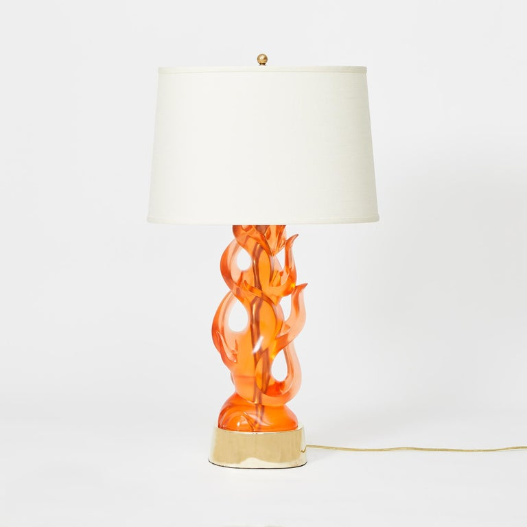 A pair of cast tangerine tinted transparent resin table lamps in the form of a flame. The oval base having a symmetrical, contemporary design, and flame-shaped elements and open sections.  Other color options available. Priced per pair.