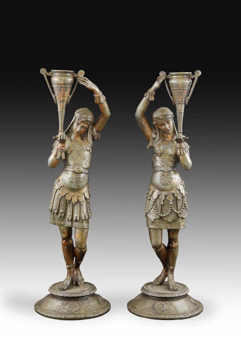 Pair of candlesticks made in calamine that preserve polychrome remains and have circular bases on which are placed two figures dressed in Roman style according to the romantic vision of the nineteenth century, each holding a vase on one of his