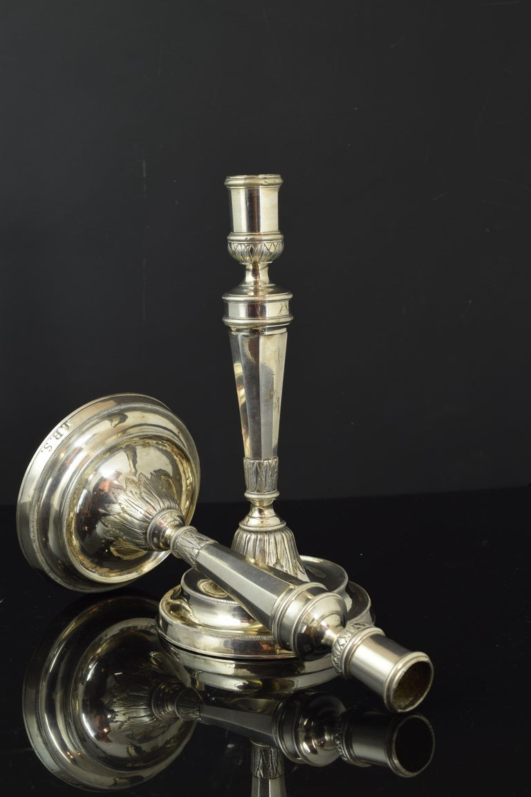 Pair of candlesticks with a circular base, in which initials are presented, with a column-shaped axis with a bell-shaped base decorated with leaves in slight relief. The shapes and moldings that decorate them respond to the influence of