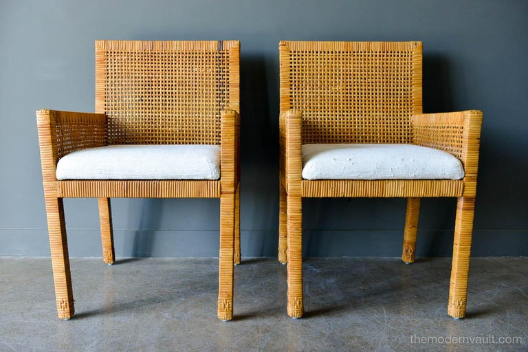 Pair of cane wrapped armchairs in the style of Billy Baldwin, circa 1970. Original silk cushions, bottom cushion is attached, back cushion is floating. Beautiful design, very comfortable chairs with great leg detail. Cane is in very good vintage