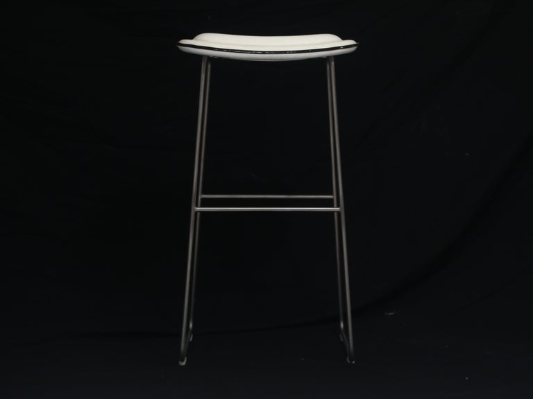 A classy and attractive pair of modern bar height barstools by Cappellini, Italy. This pair of high stools are covered in white faux leather and with a stainless steel base. Cushioned seats make these comfortable for long nights of conversations