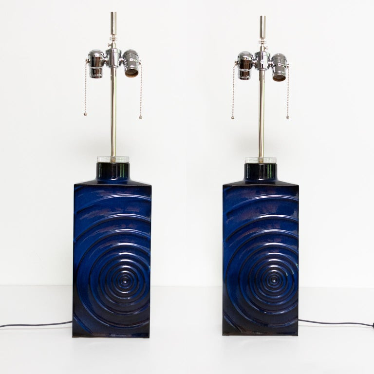 "Pair of designer Carl Zalloni ""Zykion"" lamps made by Steuler, Germany circa 1960's. The lamps are ceramic finished in a deep blue glaze and feature a raised asymmetrical circular pattern on the front and rear sides. The lamps have new chrome"