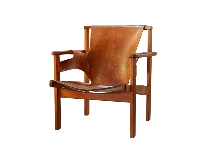 Pair of Carl Axel Acking 'Trienna' chairs in patinated brown leather, circa 1957. Executed in perfectly patinated cognac brown leather and richly grained solid oak for Nordiska Kompaniet. A quintessentially Scandinavian Modern chair by a master