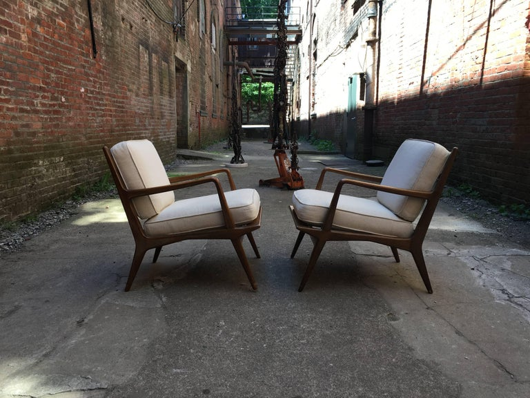 Beautiful walnut ladder back armchairs designed by Carlo di Carli for M. Singer & Sons. Elegant and sculptural pair of chairs retaining their original metal seat straps and splined rear leg detail. Upholstered white back and seat cushions. Original
