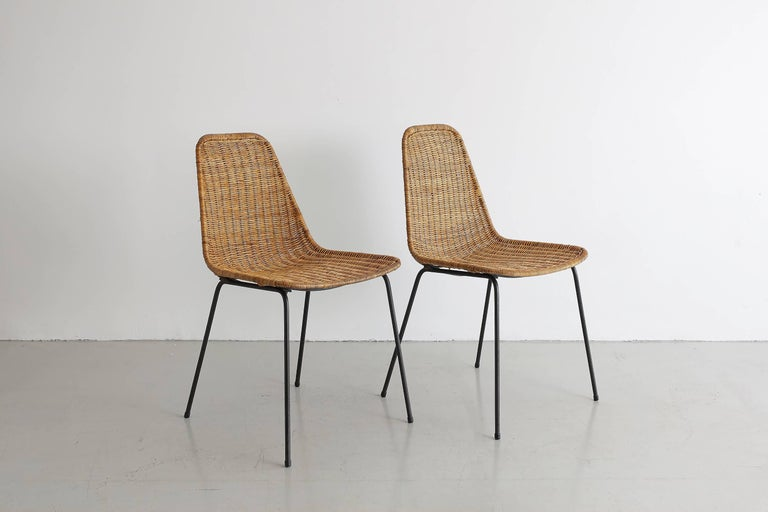 Pair of wicker chairs by Carlo Graffi & Franco Campo with inset black iron legs and bucket seats. Measures: Seat height 17
