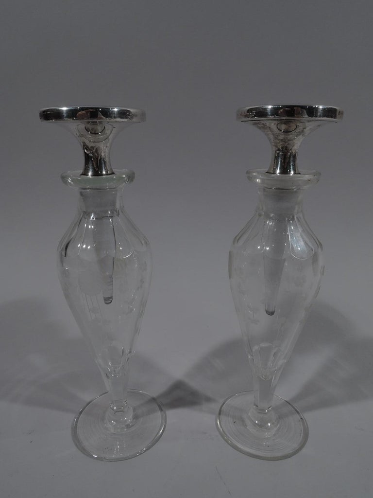 Pair of Art Deco, sterling silver, enamel, and crystal perfumes. Retailed by Cartier in New York, ca 1920. Each: Crystal baluster bottle with flat circular foot, cut lobed shoulder, and short neck. Etched stylized flowers. Disc stopper with