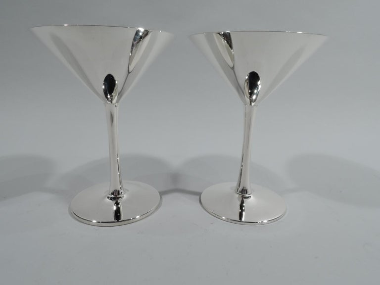 Pair of Mid-Century Modern sterling silver cocktail cups. Retailed by Cartier in New York. Each: Conical bowl on cylindrical stem mounted to circular foot. Capacious with nice balance. Fully marked including retail's stamp. One numbered 15 and the