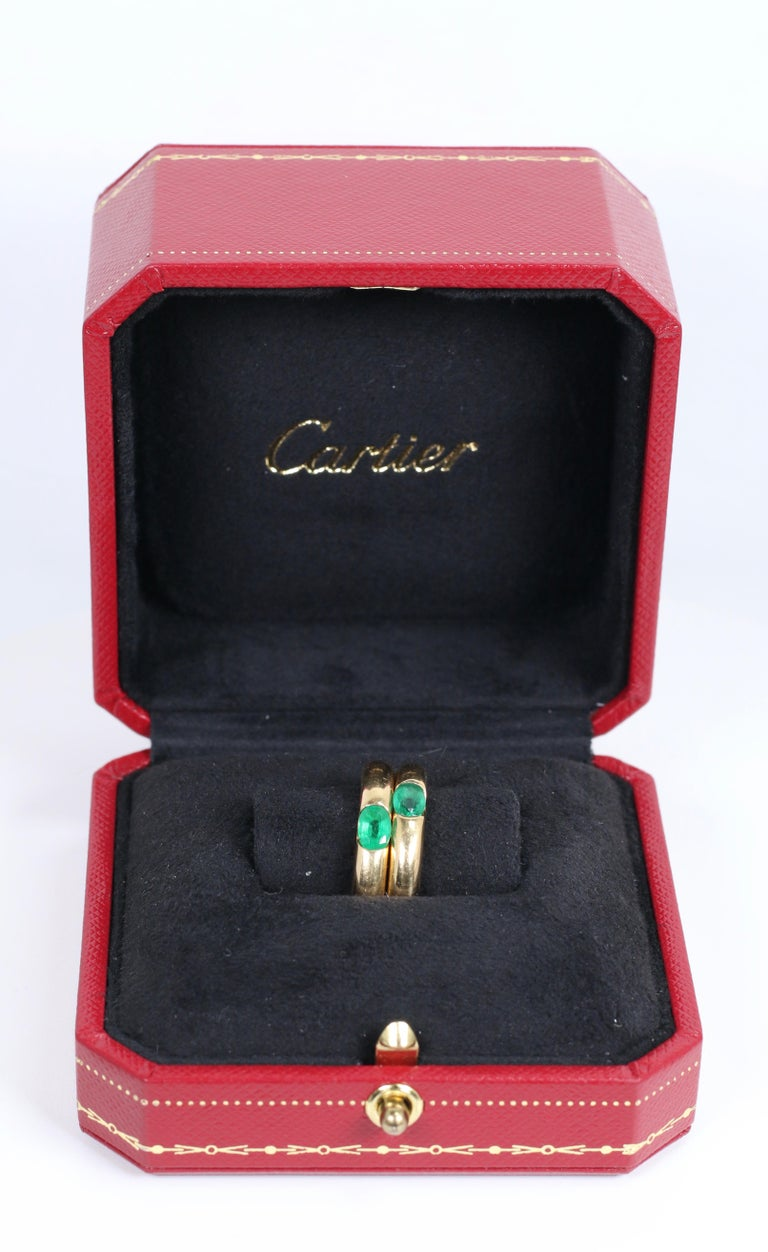 Pair of Cartier Yellow Gold Bands with Single Emeralds with Box and Papers. Size 7.25