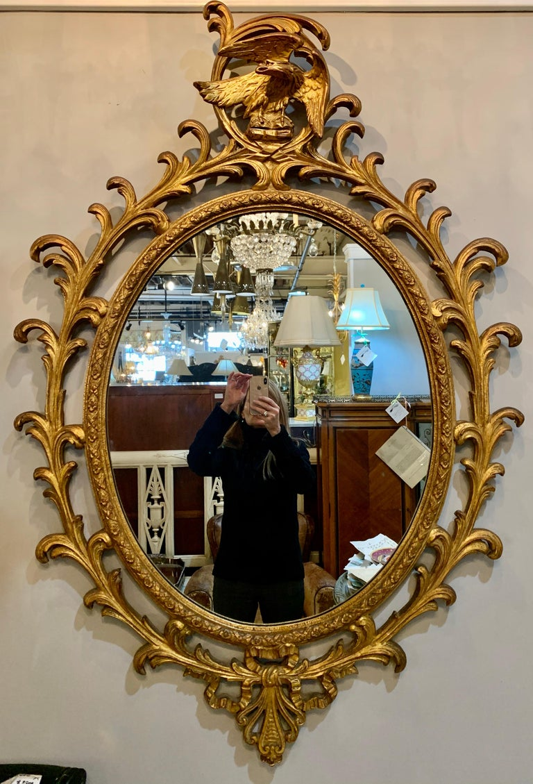 Pair of carved Italian gilt decorated wall console mirrors. Each mirror in a wonderfully carved frame with scrolls and flowers both terminating in a winged eagle.