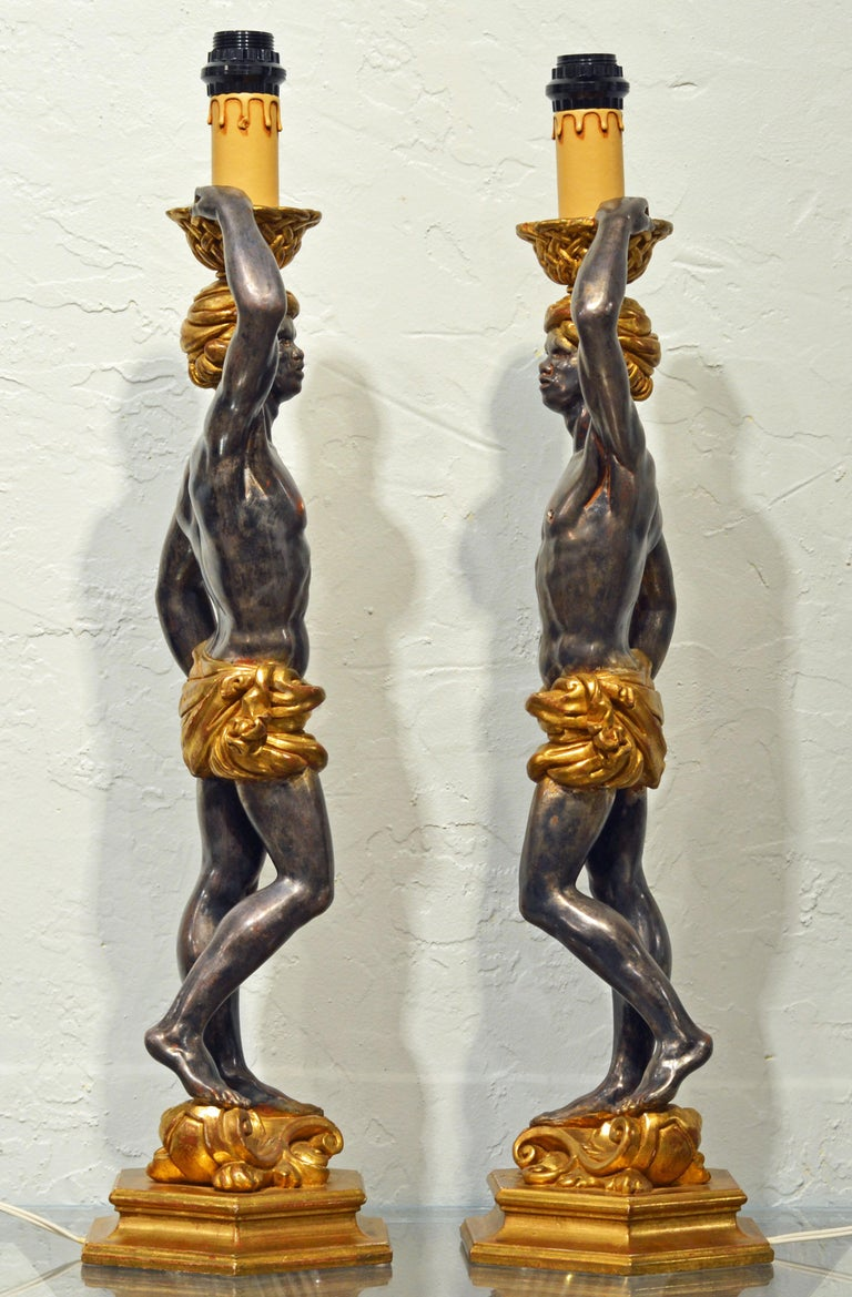 Standing more than 30 inches tall the figures wearing giltwood turbans and loin cloths are holding up baskets with simulated candles and standing on octagonal gilt woof bases. The bodies are patinated with a silvery dark finish. The lamps are wired