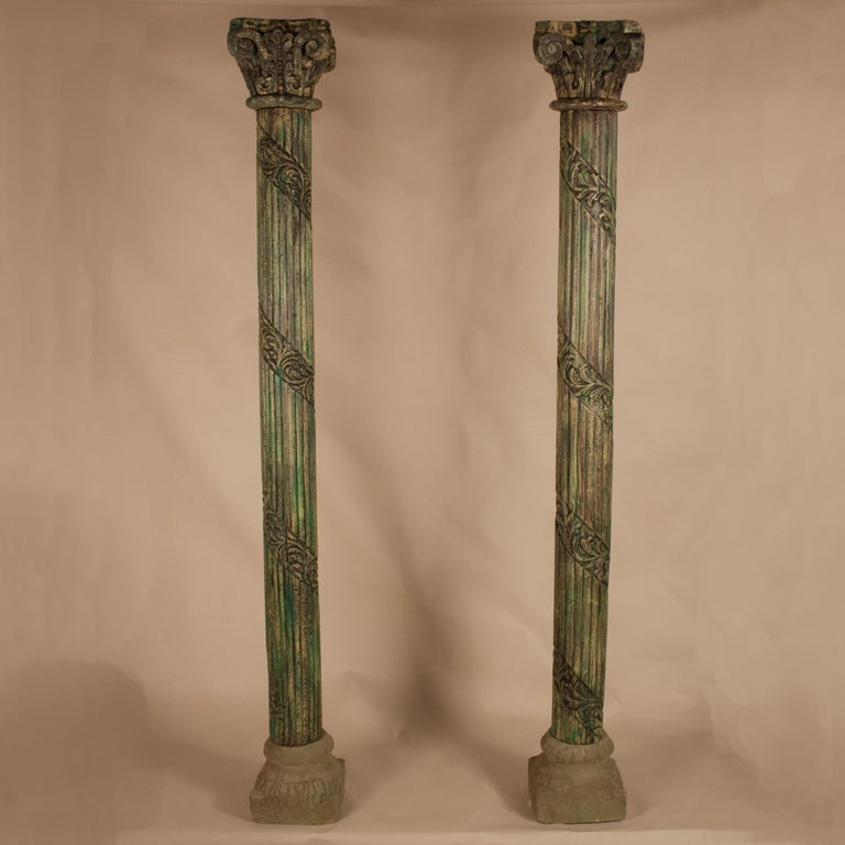 Distinctive set of teak wood columns from Gujarat, India, circa 1950, with original green paint and hand-carved, ribboned flutes and Corinthian capitals. The column bases, which have a small footprint, are made of sandstone and have weathered, yet