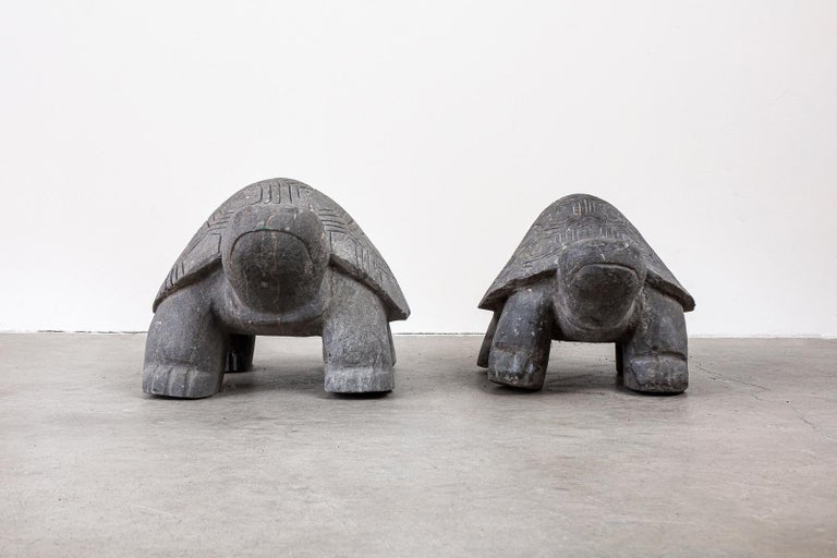 Midcentury pair of hand carved stone turtle sculptures with varying size. Decorated with geometric designs on their shells. Very heavy stone turtles perfect for your garden. Smaller turtle measures: 18