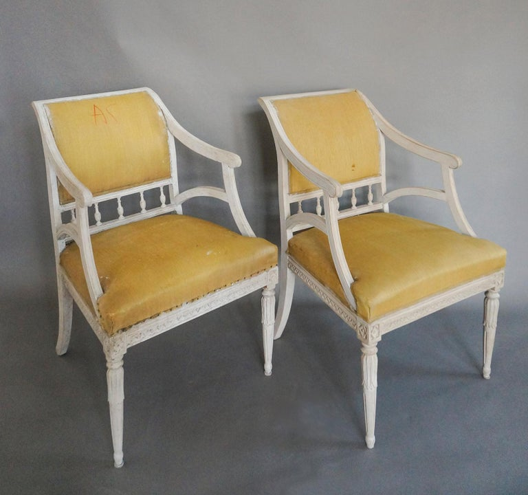Pair of armchairs with upholstered backs and seats, Sweden, circa 1900. Urn shaped spindles support the curving back, and the turned front legs have lotus carvings at the tops. Reeded arms and lambs-tongue carving around the seats. Sturdy and