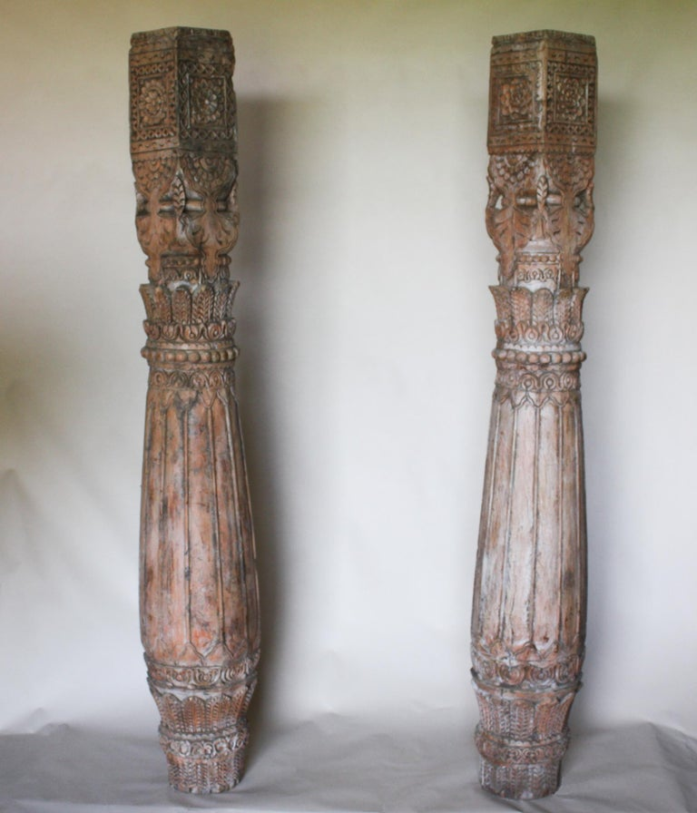 An exciting pair of hand carved teak wood pillars from Rajasthan, India. These late 19th century columns have an attractive form, wood tone and patina. Measures: Height 76.50 inches, width (at belly) 12.50 inches, width (at top) 7.50 inches, width