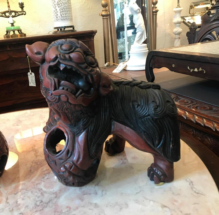 A pair of carved wood and cinnabar lacquer food dogs. The dogs, each carved with a ball in each in the mouth of the dogs and in the circular base of the front foot. Original pair that are a mirror image of each.