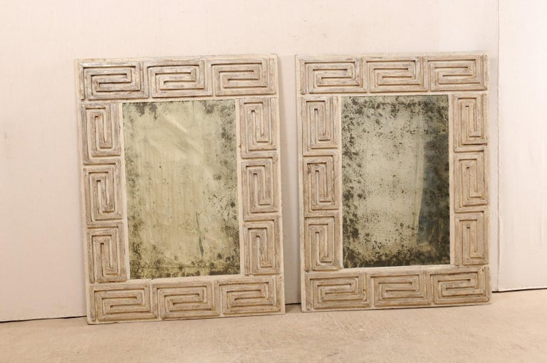 A pair of Greek key designed carved and painted wood mirrors from the 20th century. These antique mirrors, made in America, feature a thick, rectangular-shaped surround which is carved in Greek key design, with antiqued glass at each center. The