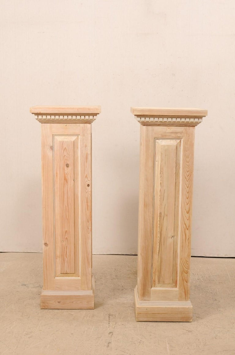 A pair of vintage American carved wood pedestal columns. This pair of bleached wood columns feature squared bodies with a single raised panel at each side, stacked molding just beneath the overhanging square-shaped top, adorn with a row of dentil
