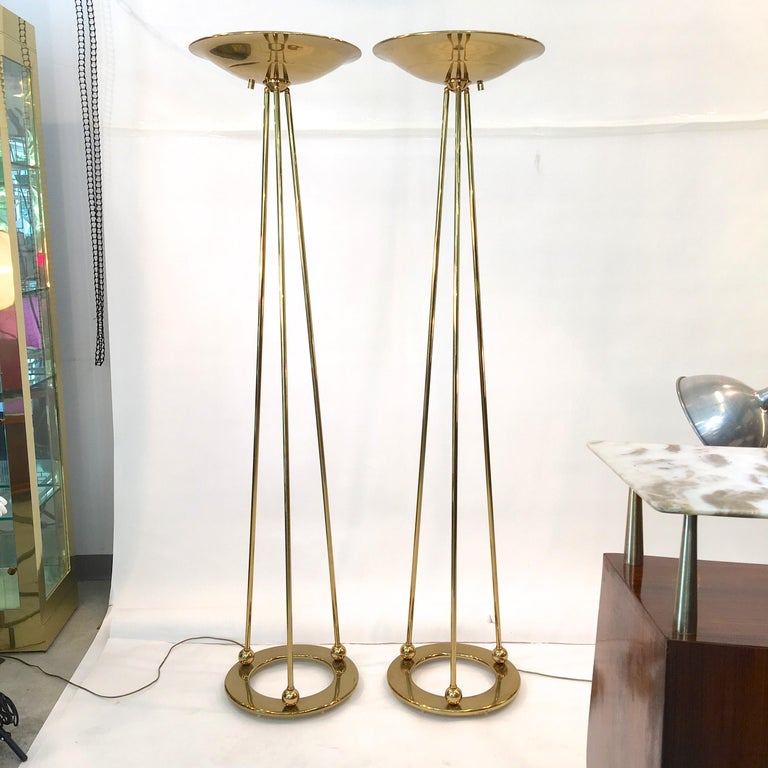 Immaculate pair of original polished brass halogen uplighter floor lamps produced by Casella Lighting in San Francisco; model Olympiad.  Very robust and impressive construction. Solid brass round ring base with three brass rods which connect to