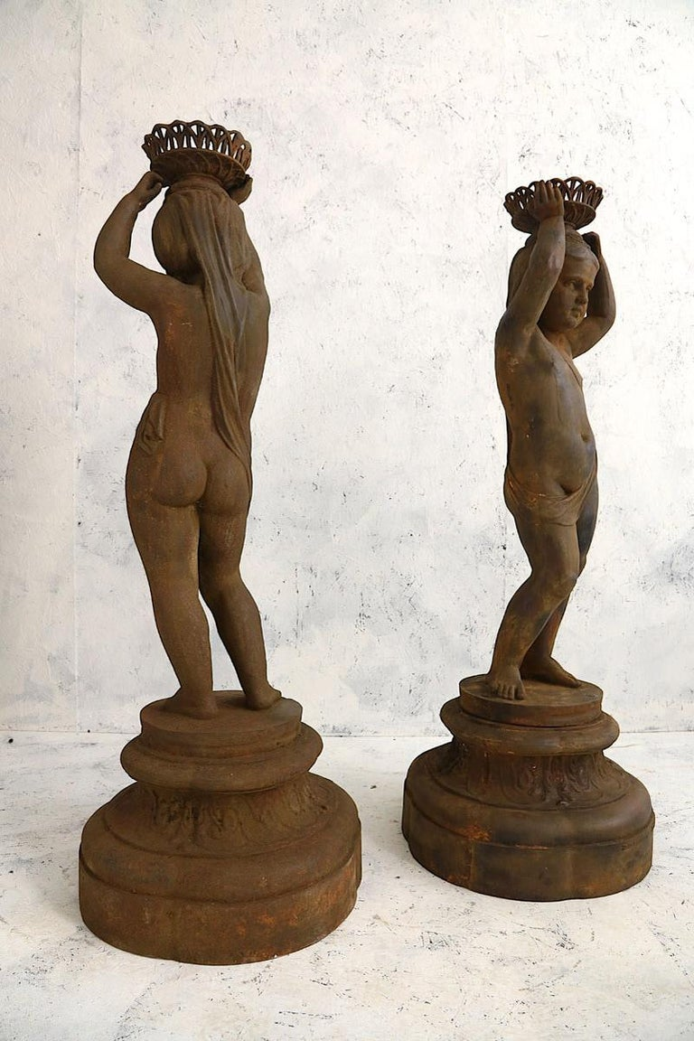 Pair of cast iron figures of girls with baskets attributed to J.J. Ducel Maitre de Forges Paris mounted on a Stockholm Foundry stamped base. These Cast Iron figures of girls work well both externally in the garden or has internal statues