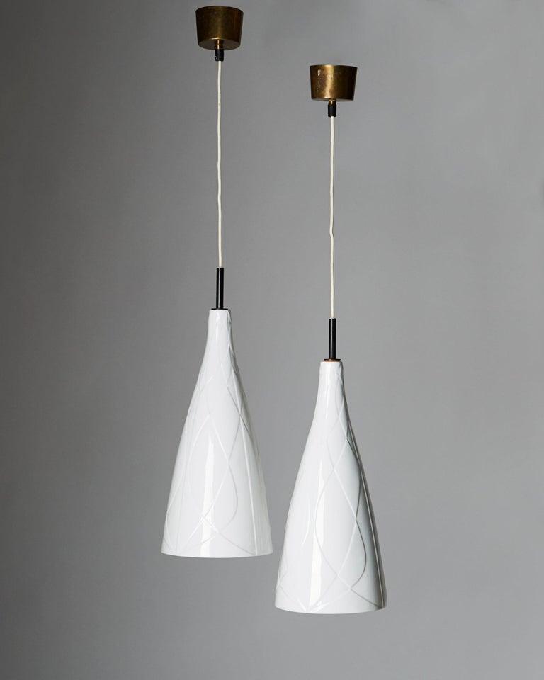 Brass and porcelain.  Sold as a pair.  Measures: L 53 cm/ 21'' D 20 cm/ 8''.
