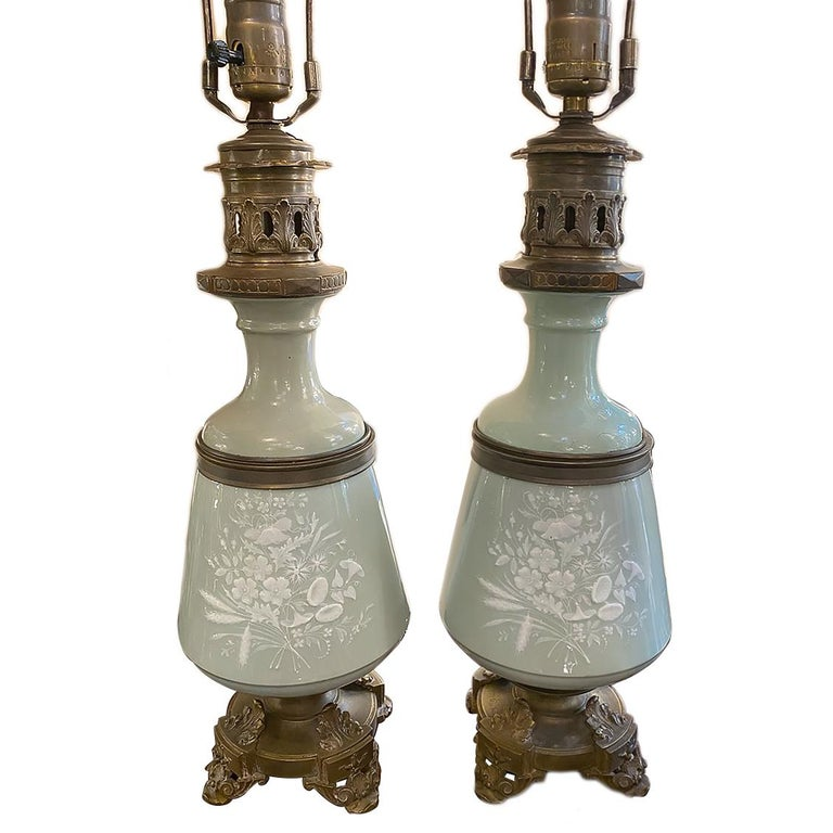 A pair of turn-of-the-century French celadon table lamps with floral decoration, bronze bases and fittings.  Measurements: Height of body: 17.5